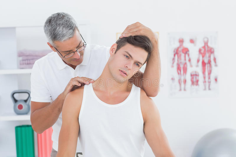 Doctor doing neck adjustment. In medical office stock image