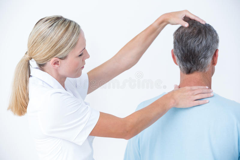 Doctor doing a neck adjustment. In medical office stock photo