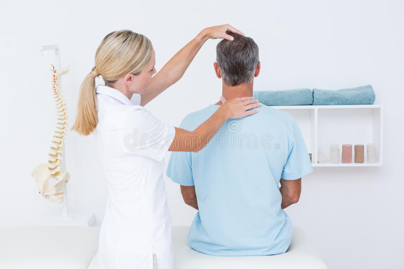 Doctor doing neck adjustment. In medical office stock photo