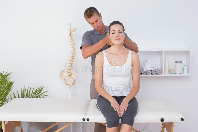 Doctor doing neck adjustment. In medical office stock images