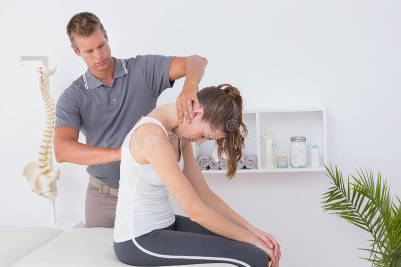 Doctor doing neck adjustment. In medical office royalty free stock image