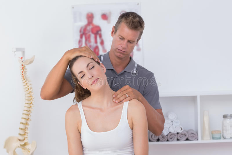 Doctor doing neck adjustment. In medical office royalty free stock photos