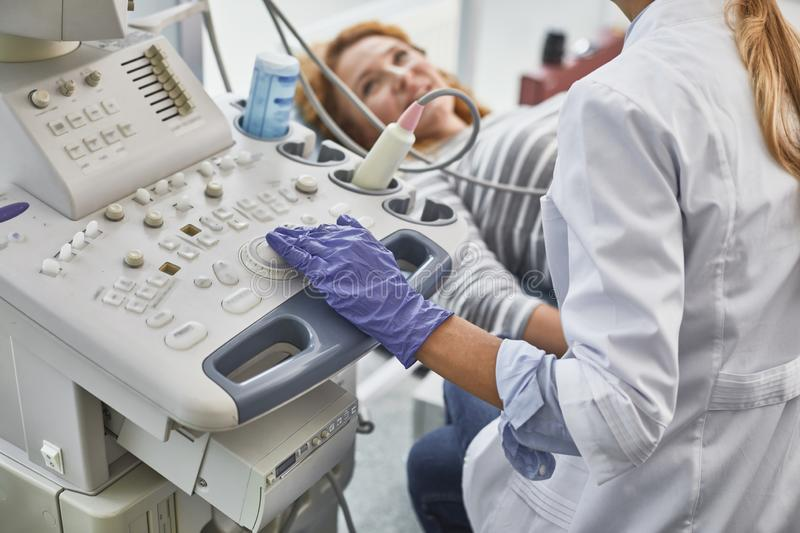 Doctor doing sonogram procedure for mature lady stock photos