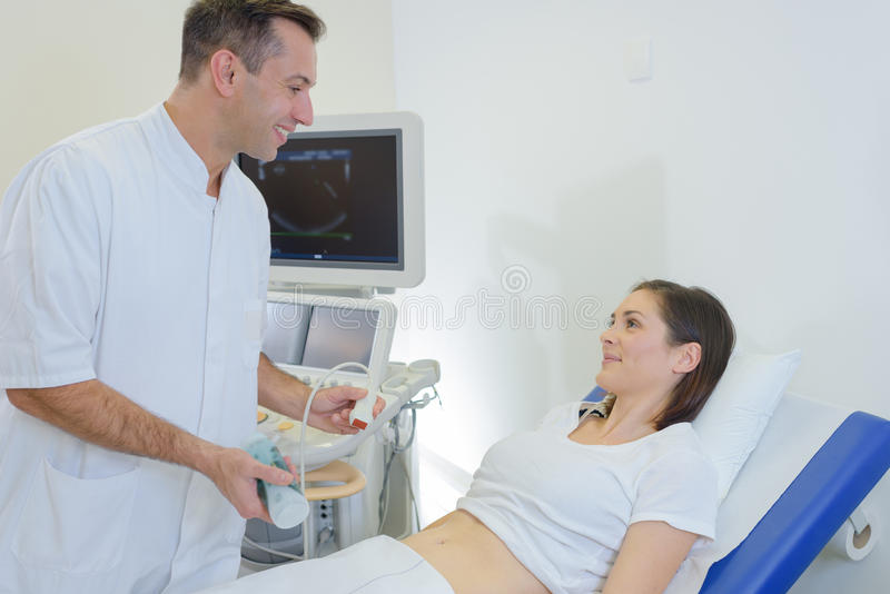Doctor doing ultrasound on belly pregnant woman in clinic. Doctor doing ultrasound on belly of pregnant women in clinic royalty free stock image