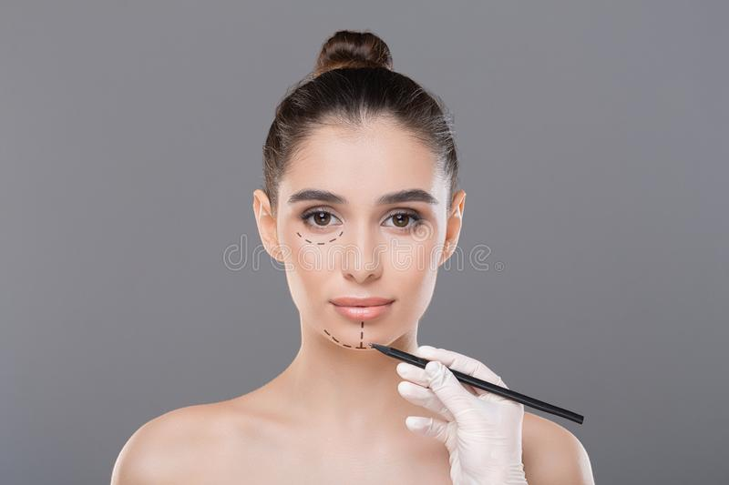 Doctor drawing lines on female patient`s face before skin lifting. Beauty procedure. Doctor drawing lines on female patient`s face before skin lifting, gray royalty free stock photo
