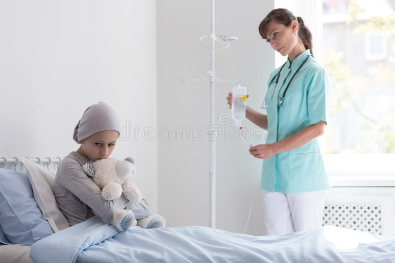 Doctor with drip visiting sad sick girl with cancer in the hospital. Doctor with drip visiting sad sick girl with cancer hugging plush toy in the hospital royalty free stock image