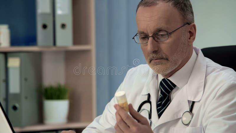 Doctor dudoso que mira las píldoras, medicinas falsificadas de la mal calidad, placebo foto de archivo
