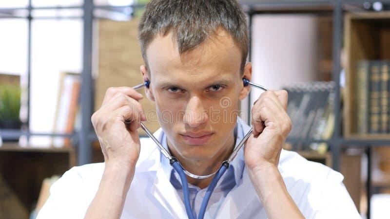 Doctor el estetoscopio de Wearing en los oídos, listos para comprobar al paciente fotos de archivo libres de regalías