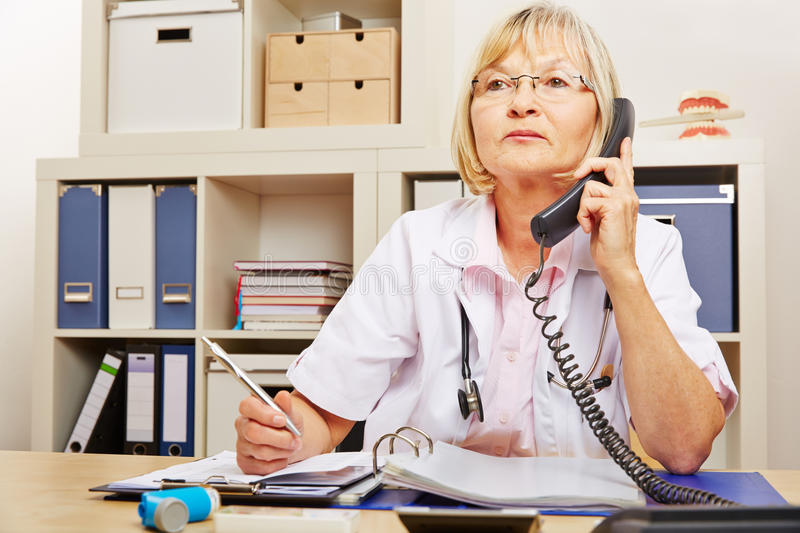 Doctor at emergency service telephone stock photography