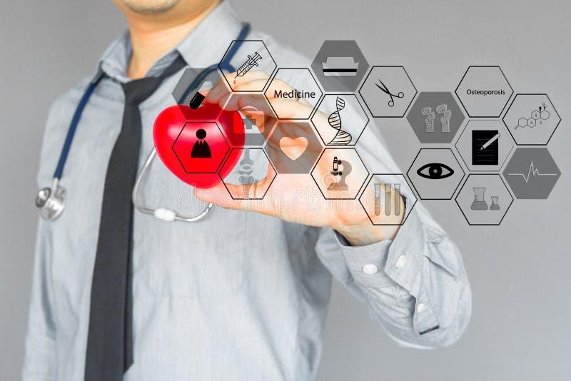 Doctor en camisa gris y lazo negro Llevar a cabo el corazón rojo con infographic médico en gris fotos de archivo