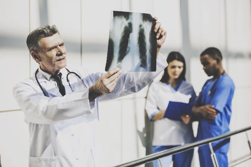 Doctor en radiografía que se sostiene uniforme del blanco en hospital foto de archivo