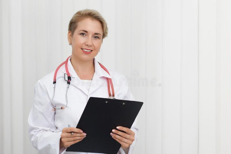 Doctor en uniforme y con la presentación del estetoscopio fotos de archivo libres de regalías