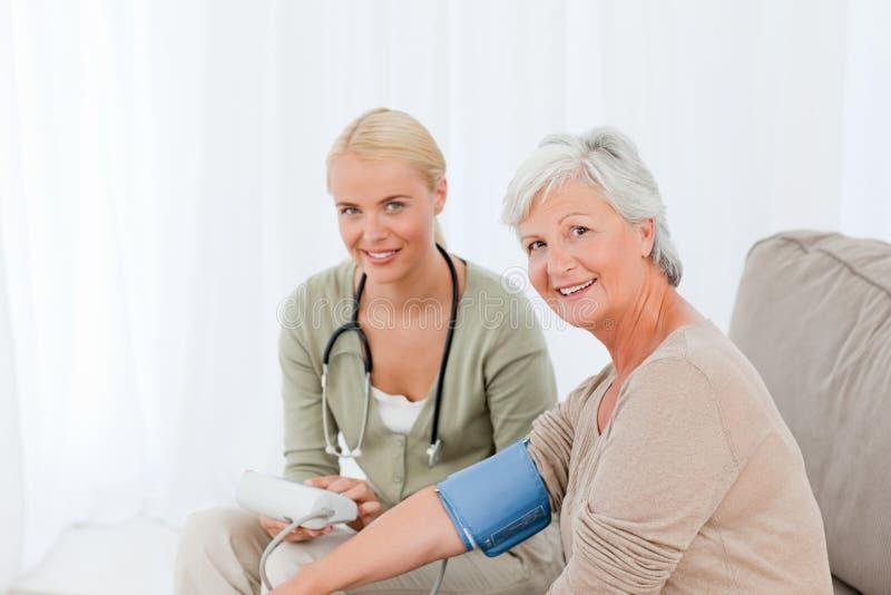 Doctor encantador que toma la presión arterial imagen de archivo libre de regalías