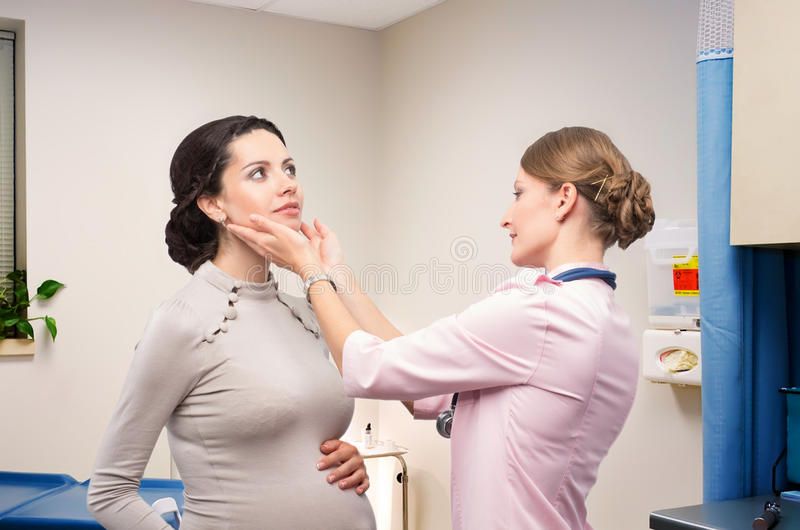 Doctor endocrinologist checking thyroid pregnant royalty free stock images