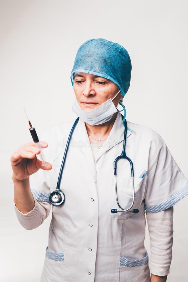Doctor enfocado que sostiene la jeringuilla foto de archivo