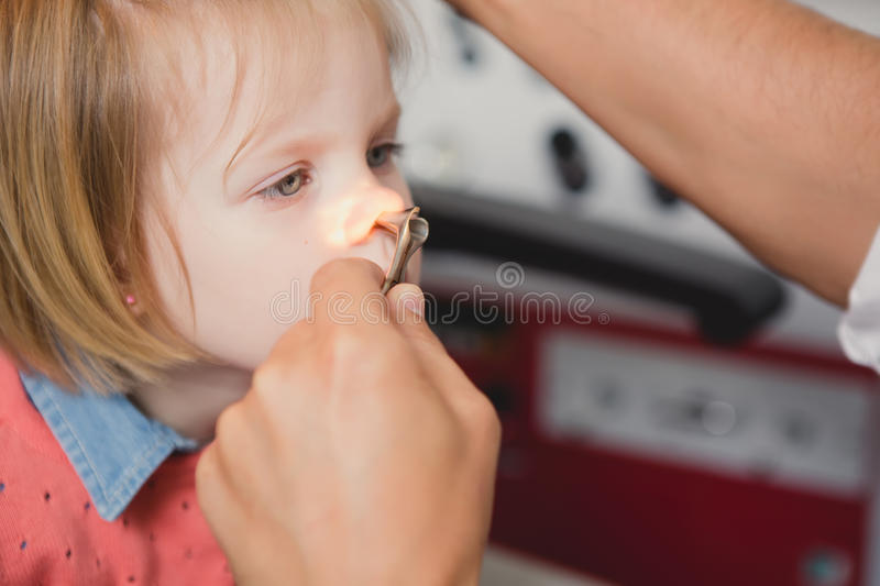 Doctor ENT checking ear with otoscope to girl patient. At hospital royalty free stock photography