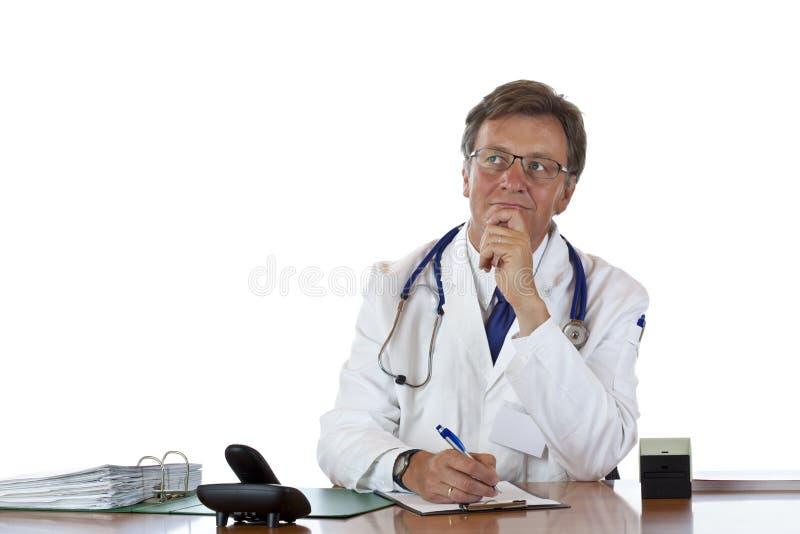 Doctor envejecido contemplativo en el escritorio fotografía de archivo