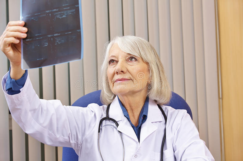 Doctor evaluating x-ray image in office. Senior doctor evaluating x-ray image in her office royalty free stock image