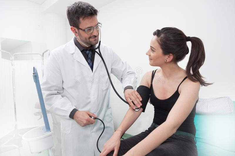 Doctor examination of a young lady with stethoscope. A dark hair doctor in white coat controling cardio of a women patient with stethoscope in the medical room royalty free stock photos