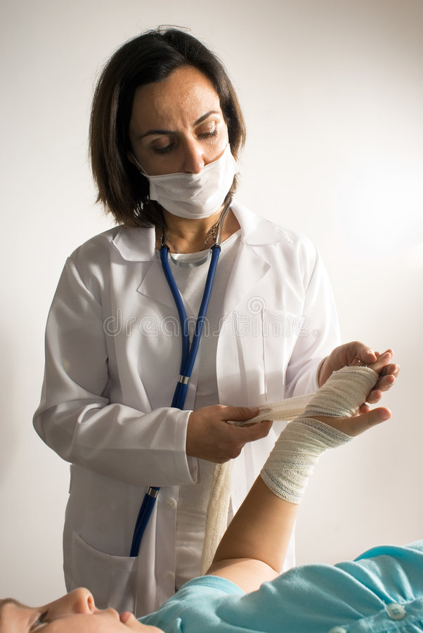 Download Doctor Examines A Bandaged Arm Stock Image - Image of midlife, people: 5413443