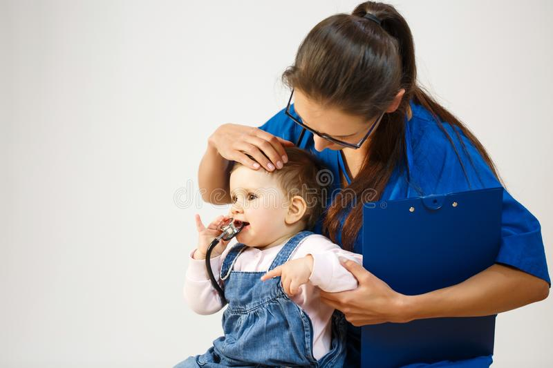 The doctor examines the child while he nibbles at the stethoscope stock image