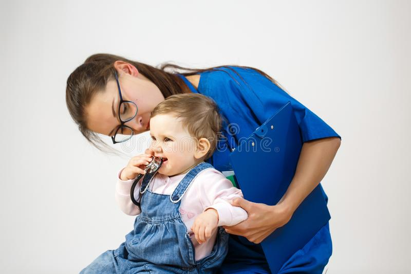 Doctor examines the child while he plays with a stethoscope royalty free stock image