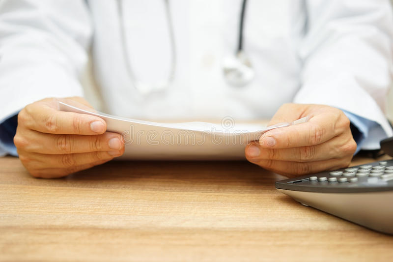 Doctor examines diagnose. Doctor is examining diagnose and will call the patient stock photo