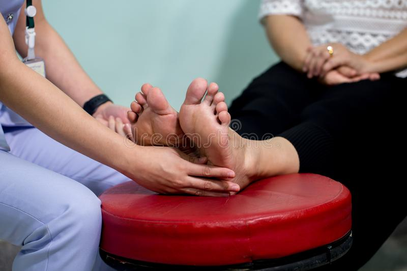 The doctor examines the nerve response with monofilament odiatrist treating feet during procedure. Doctor neurologist examining fe. Male patient stock photo