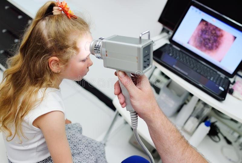 The doctor examines the special medical device moles child stock photography