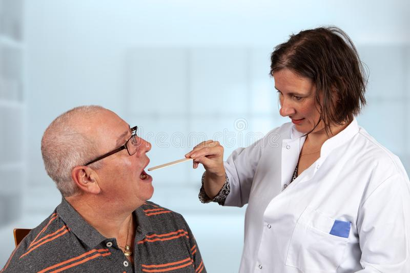 Doctor examines throat with a tongue spatula. Doctor examines the patiënt by looking in his throat with a tongue spatula royalty free stock photos