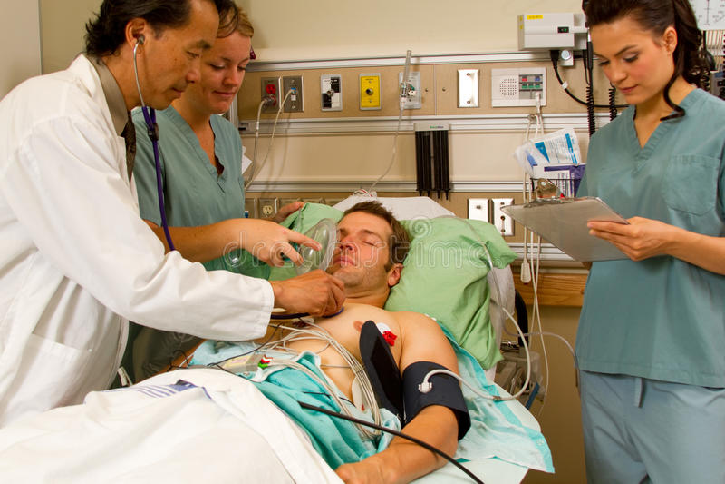Doctor examing patient, nurse applying oxygen stock photography