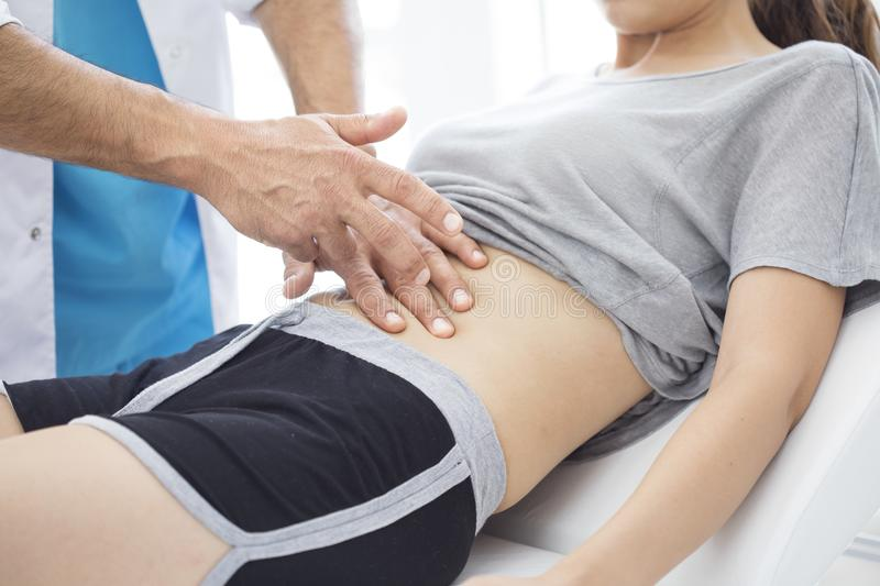Doctor is examining the abdomen of patient stock photography