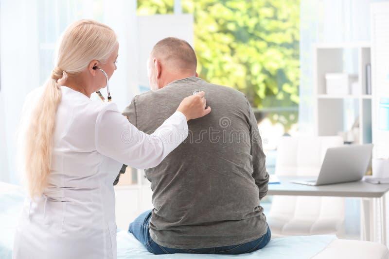 Doctor examining coughing mature man stock photos