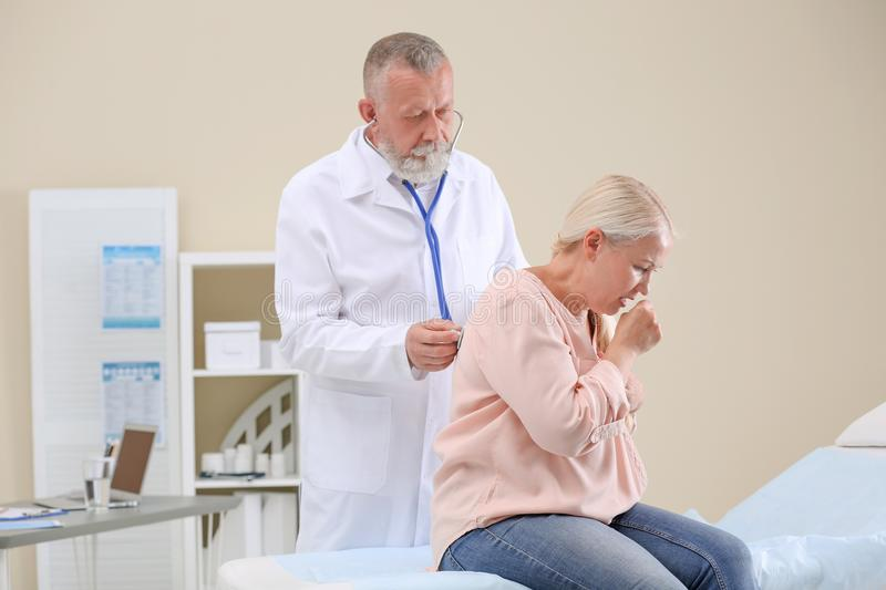 Doctor examining coughing mature woman royalty free stock photography