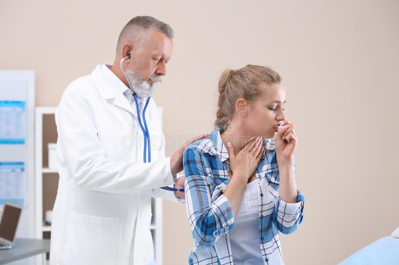 Doctor examining coughing young woman. Doctor examining coughing young women at clinic stock photos