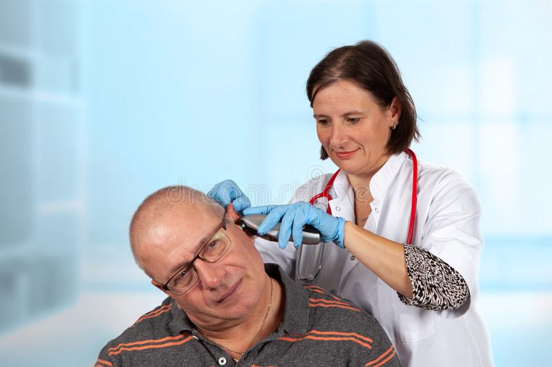 Doctor examining ear with otoscope. Doctor is looking in the ear of a patiënt with an otoscope to examine the inner ear royalty free stock photography