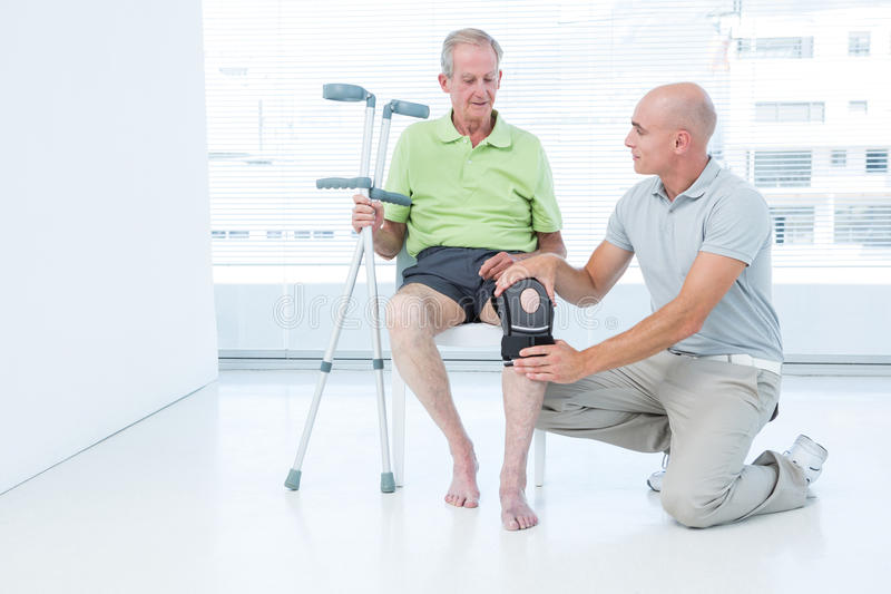 Doctor examining his patient knee stock image