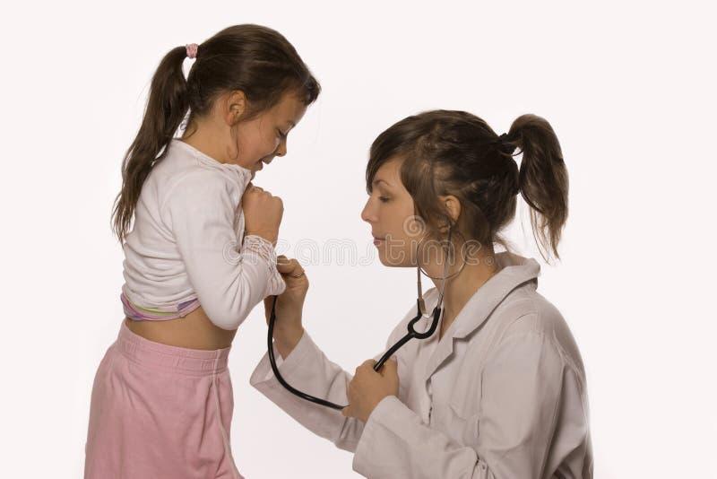 Doctor examining little girl. Female doctor with stethoscope examinig girl. Isolated on white stock photo