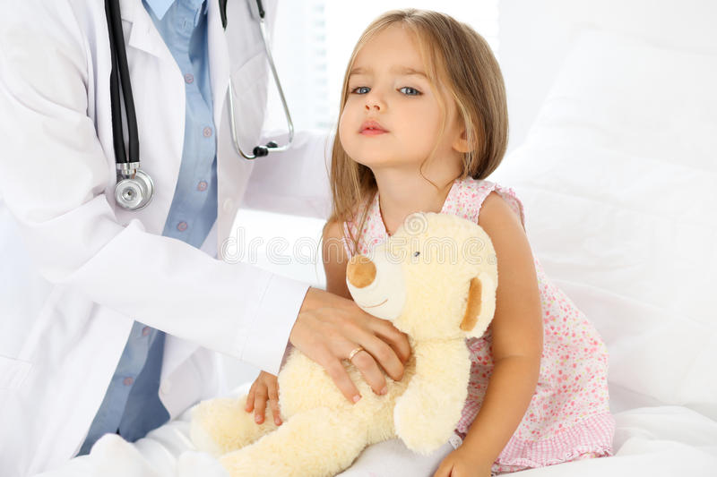 Doctor examining a little girl by stethoscope royalty free stock images