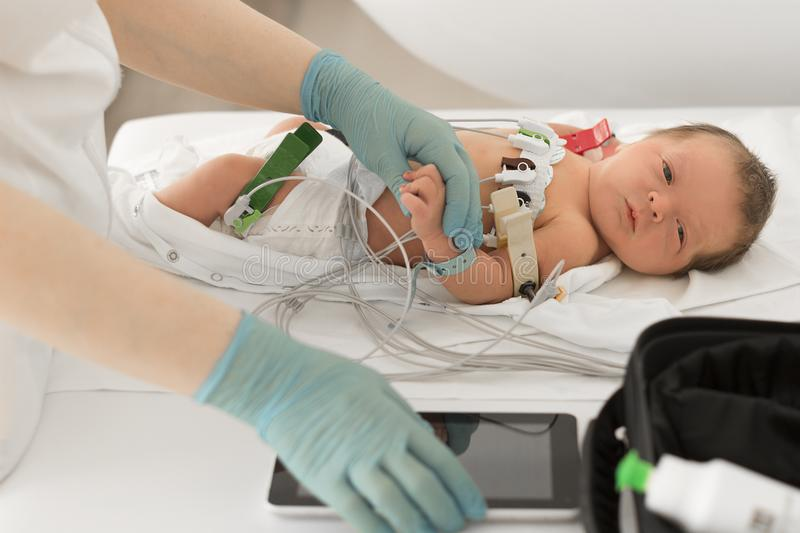 Doctor examining little newborn with cardio equipment in clinic. Baby health concept stock images