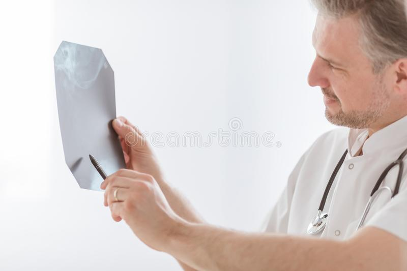 Doctor examining lung`s x-ray at bright hospital office stock images