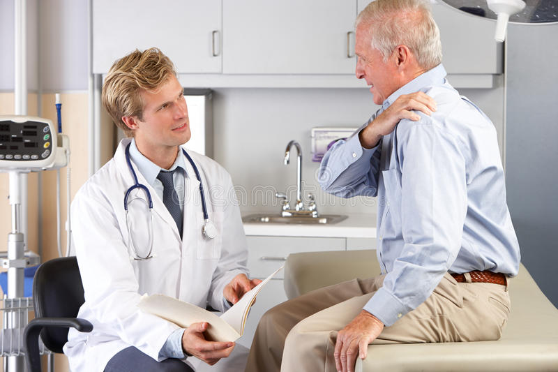 Doctor Examining Male Patient With Shoulder Pain royalty free stock photos