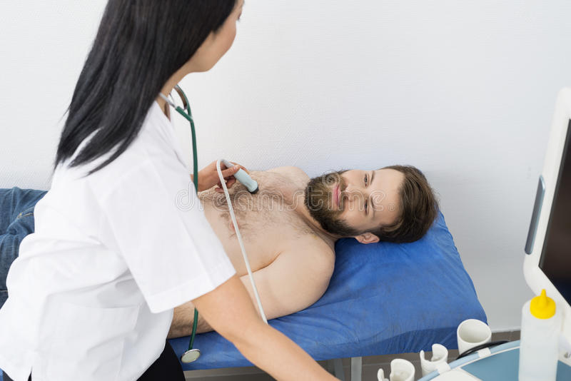 Doctor Examining Male Patient With Ultrasound Machine. High angle view of female doctor examining male patient with ultrasound machine in hospital stock photography