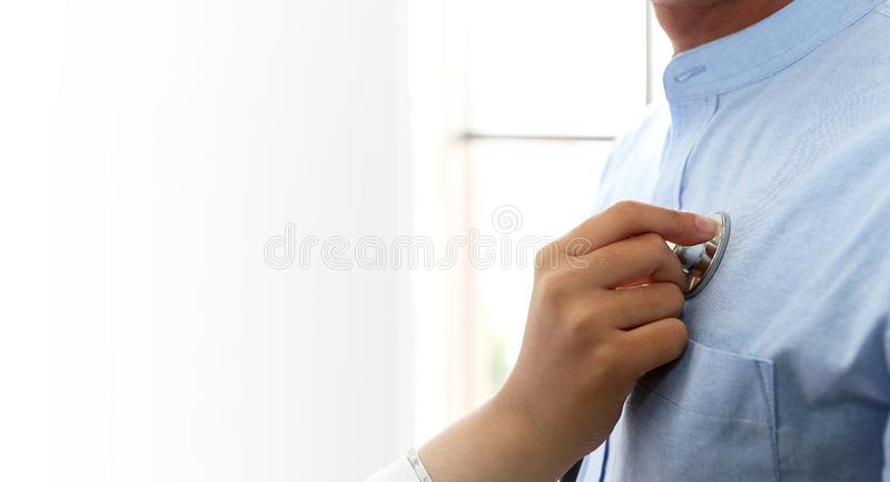 Doctor examining a man in a hospital. Stethoscope doctor. Close stock photo