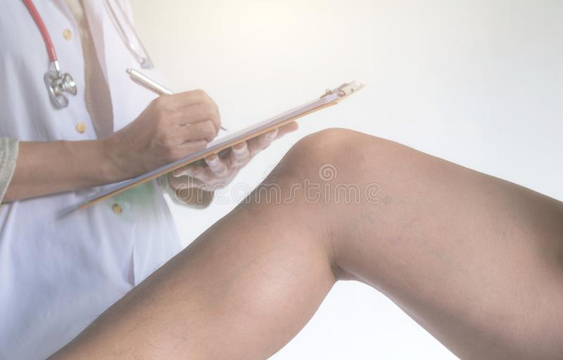 Doctor examining man leg at the hospital. Physiotherapist checking to the leg of patient. royalty free stock photos