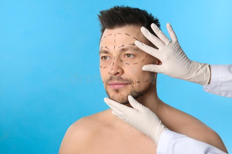 Doctor examining man`s face before plastic surgery operatio stock image