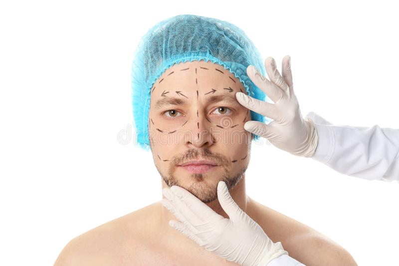 Doctor examining man`s face before plastic surgery operation on white royalty free stock images