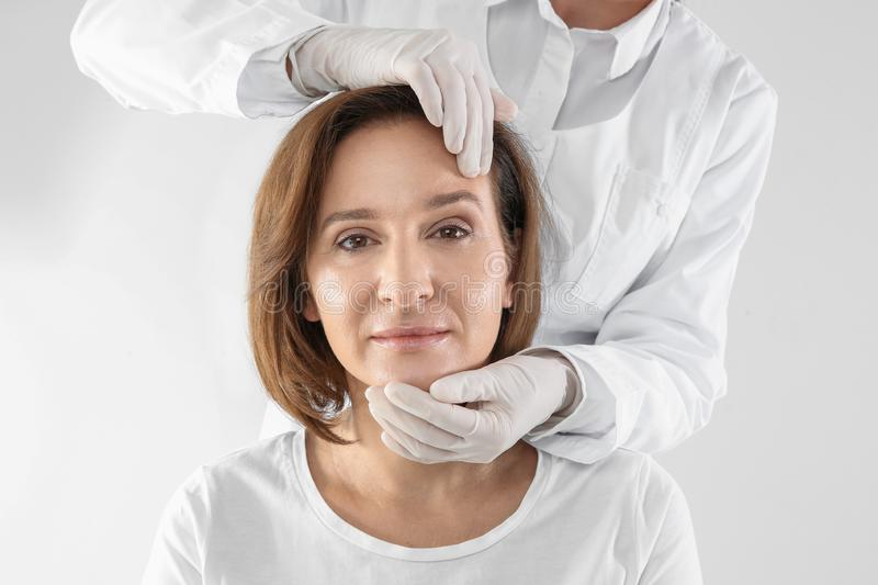 Doctor examining mature woman face before surgery on white background stock images