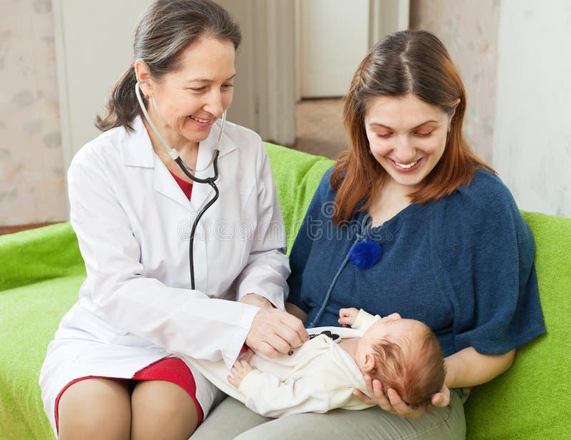 Doctor examining newborn baby with phonendoscope. Friendly mature pediatrician doctor examining newborn baby with phonendoscope royalty free stock images