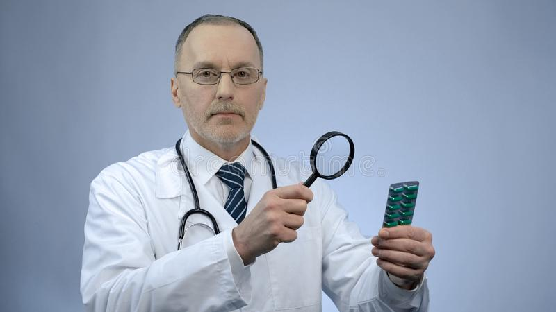 Doctor examining pack of pills with magnifying glass, counterfeit medication royalty free stock images